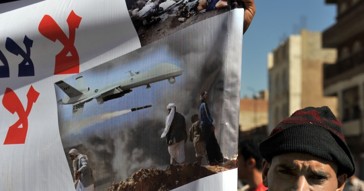 A Yemeni man holds a banner during a protest against United States drone strikes on Yemen close to the home of Yemeni President Abdrabuh Mansur Hadi, in the capital Sana'a, on Jan. 28, 2013.</p>