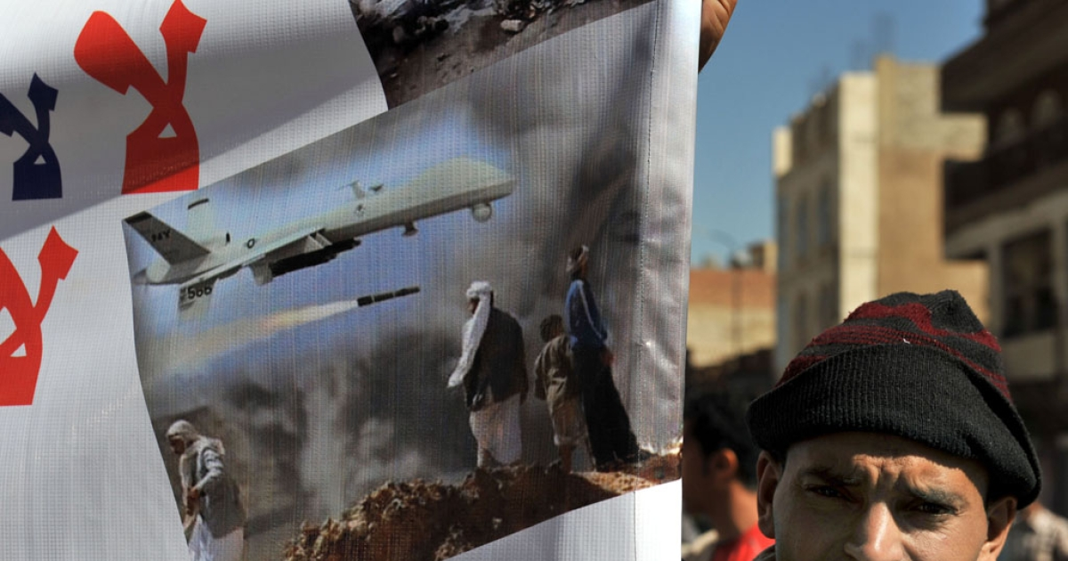 A man holds a banner protesting US drone attacks on Yemen near Yemeni President Abdrabuh Mansur Hadi in the capital Sanaa on January 28, 2013.</p>