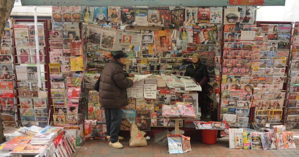 A newspaper vendor (R) talks to a customer at her booth on a street in Shanghai on Jan. 8, 2013. In December, China announced that it would expel dozens of foreign reporters from the country, in an unprecedented crackdown by authorities against foreign news organizations.</p>