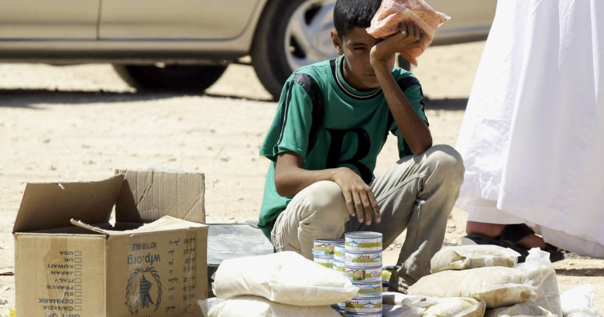 A young Syrian refugee boy sells canned tuna and other food items in the Zaatari refugee camp, located close to the Jordanian city of Mafraq, near the border with Syria, on September 4, 2013.</p>