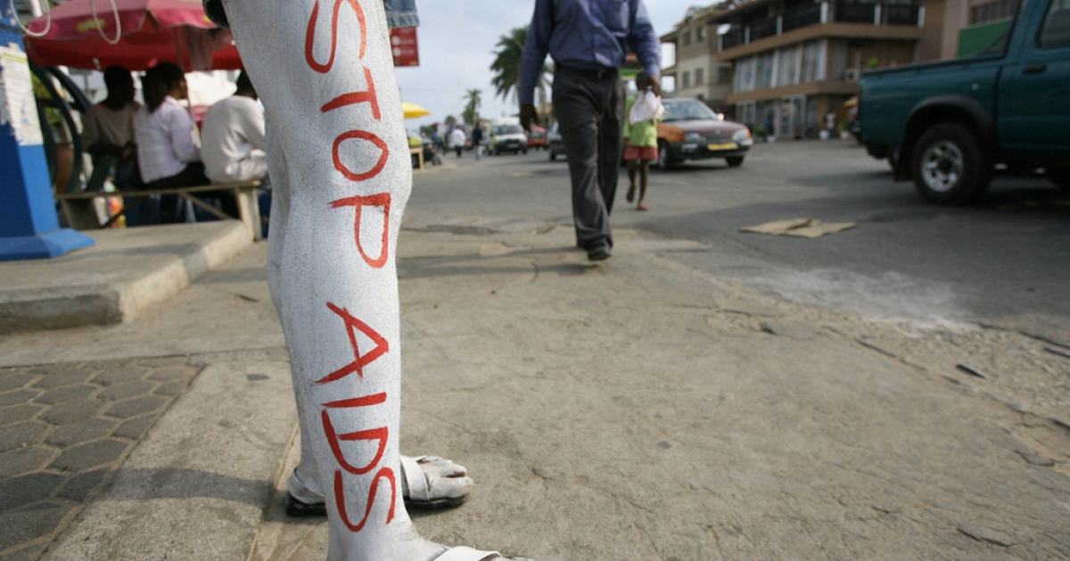 A man walks in Accra past a Ghanaian volunteer campaigning against AIDS.</p>