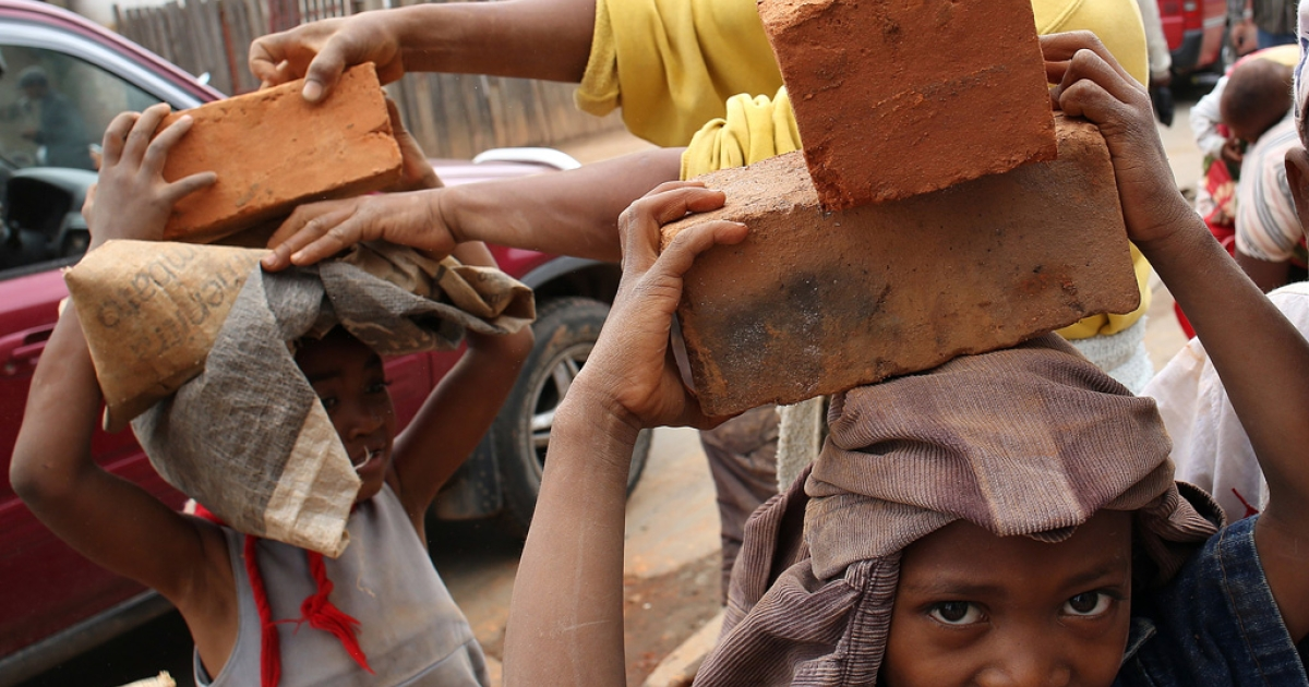 Children carry bricks on December 19, 2013 in Antananarivo, ahead of the upcoming presidential election.</p>