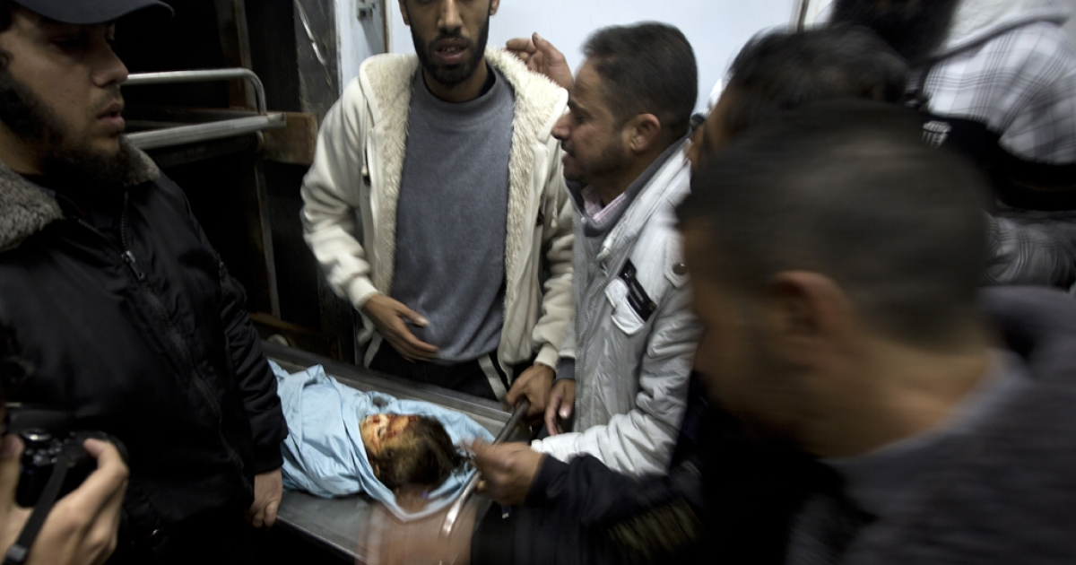 A relative of three-year-old Palestinian girl Hala Abu Sabikha identifies her as she lies in the morgue of a hospital in Deir al-Balah in the central Gaza Strip on December 24, 2013.</p>