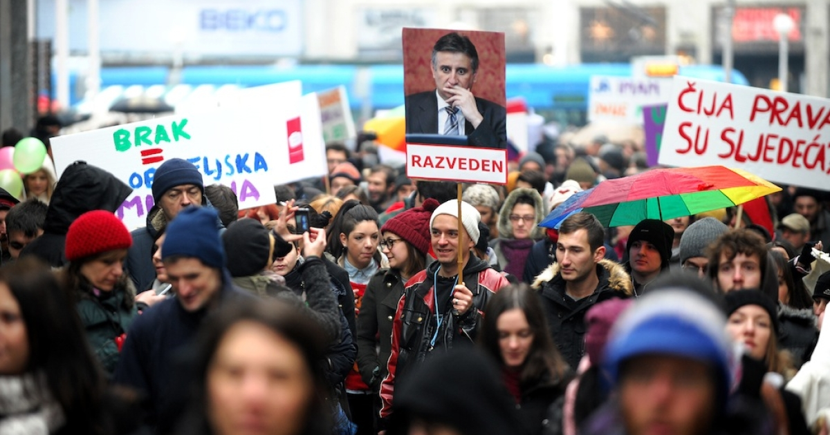 Croatian gay rights supporters hold a picture of Tomislav Karamarko, leader of the conservative opposition Croatian Democratic Union party, reading 'Divorced' as they gather for a protest in Zagreb on November 30, 2013 on the eve of a constitutional referendum that could outlaw same-sex marriage in the EU's newest member state.</p>