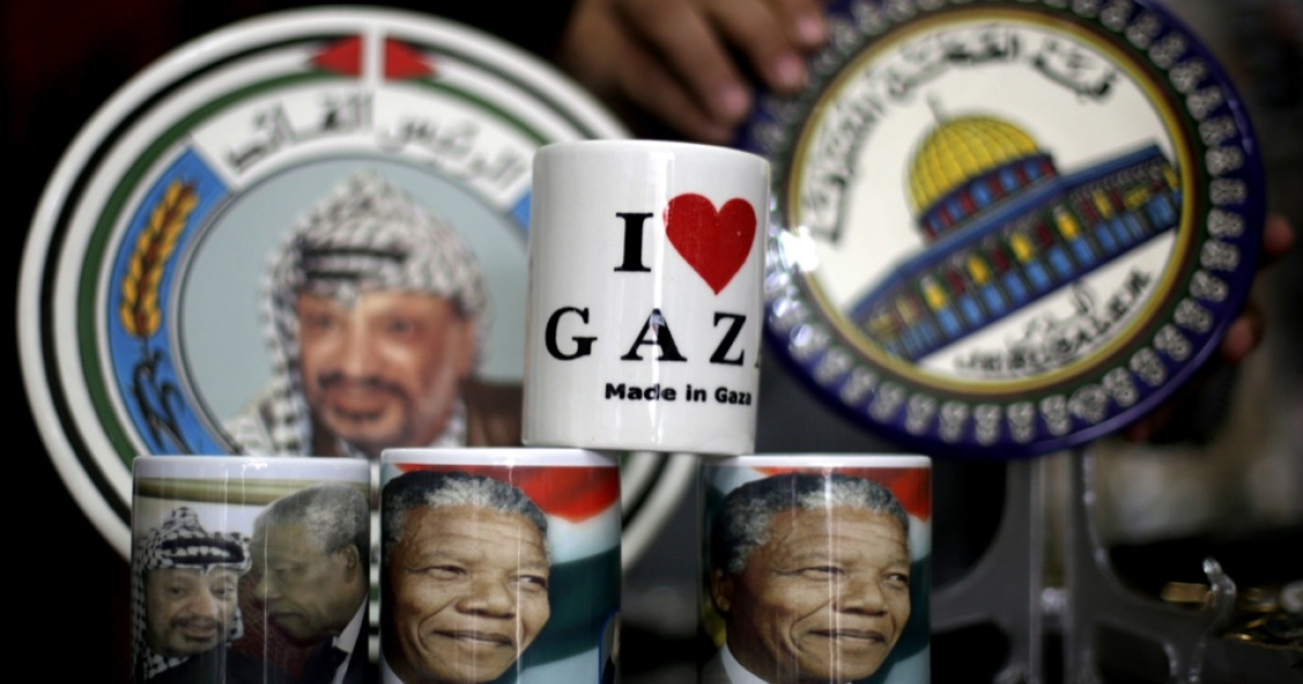 A vendor displays cups bearing the portrait of late South African leader Nelson Mandela and late Palestinian leader Yasser Arafat in Gaza City on Dec. 10, 2013.</p>