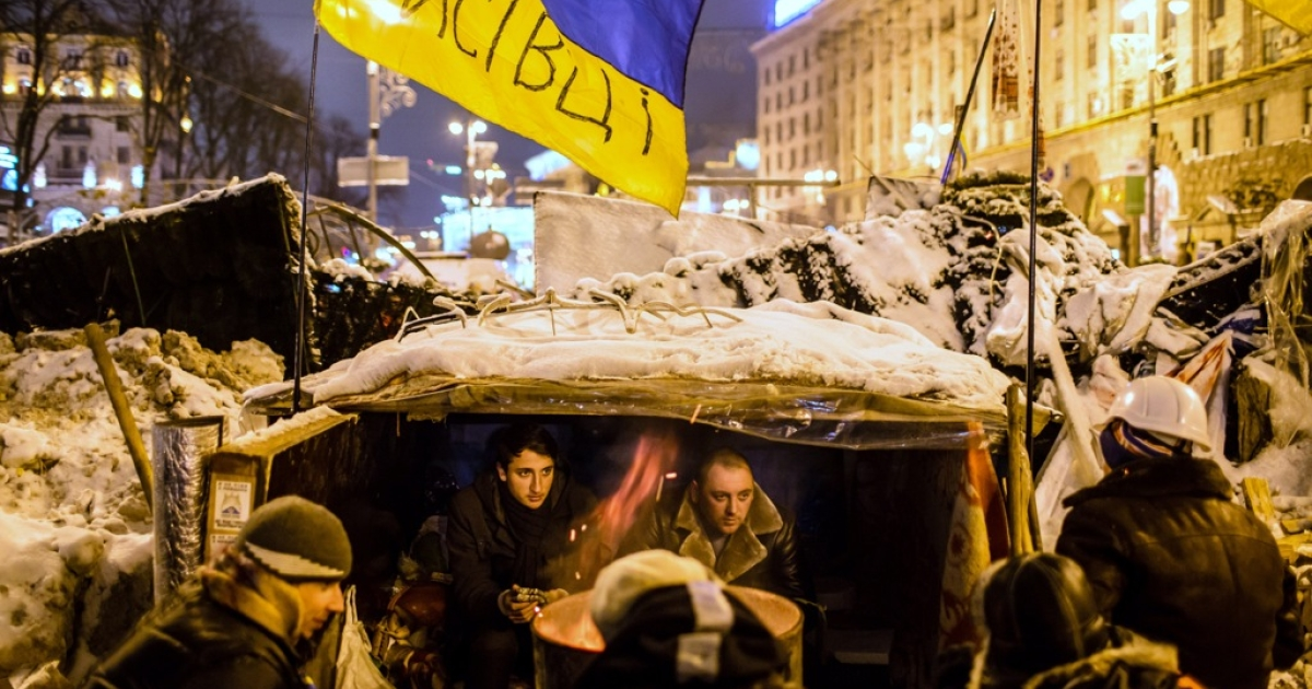 Ukrainian anti-government protesters hunker down in a makeshift shelter built into a barricade near Kyiv's Independence Square on December 11, 2013.</p>