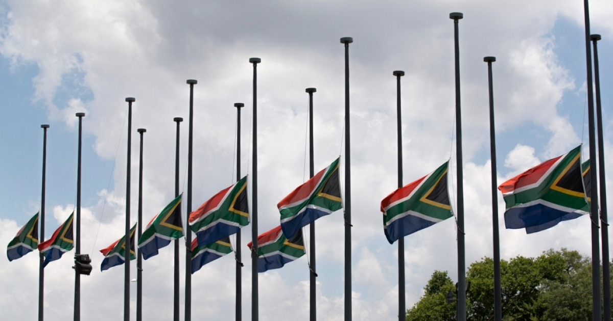 South African flags fly at half-mast as the body of former South African president Nelson Mandela lies in state for a final day at Union Buildings in Pretoria on Dec. 13, 2013.</p>
