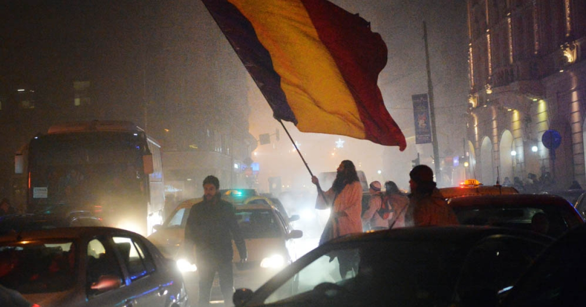 Romanian protesters shouts anti governmental slogans and wave a Romanian flag during a protest against Romanian politicians in Bucharest December 15, 2013.  A top leader of Romania's ruling coalition said snap amendments granting lawmakers immunity from graft charges should be cancelled by a new vote after sparking international criticism.</p>