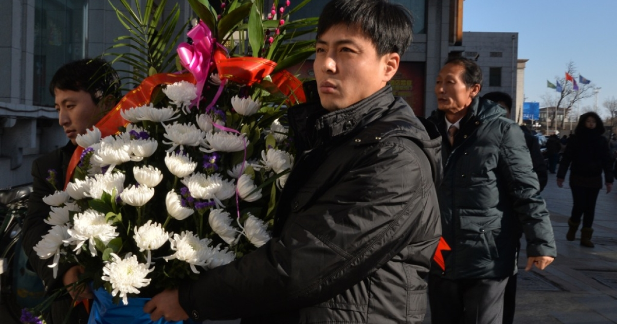 North Koreans take flowers to the North Korean Consulate in the Chinese border town of Dandong to pay their respects on the second anniversary of the death of former leader Kim Jong Il, on December 17, 2013.</p>