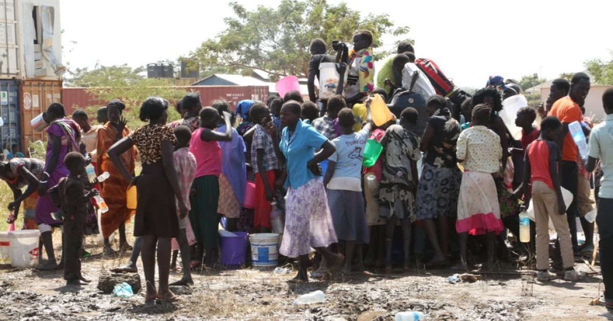 People displaced following fighting in the South Sudanese capital queue to collect water inside the UN mission's compound there, on December 17, 2013, on the outskirts of Juba.</p>