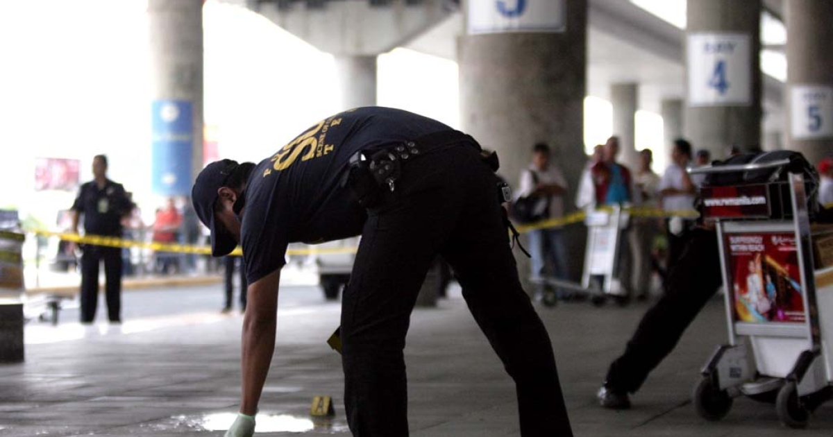 A policeman inspects the crime scene after gunmen opened fire outside the Manila International Airport in Manila on December 20, 2013.</p>