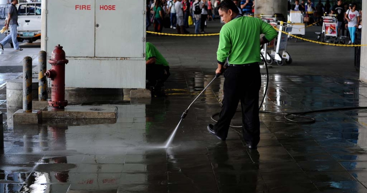 A maintenance crew worker cleans the crime scene after gunmen opened fire outside the Manila International Airport in Manila on December 20, 2013.</p>