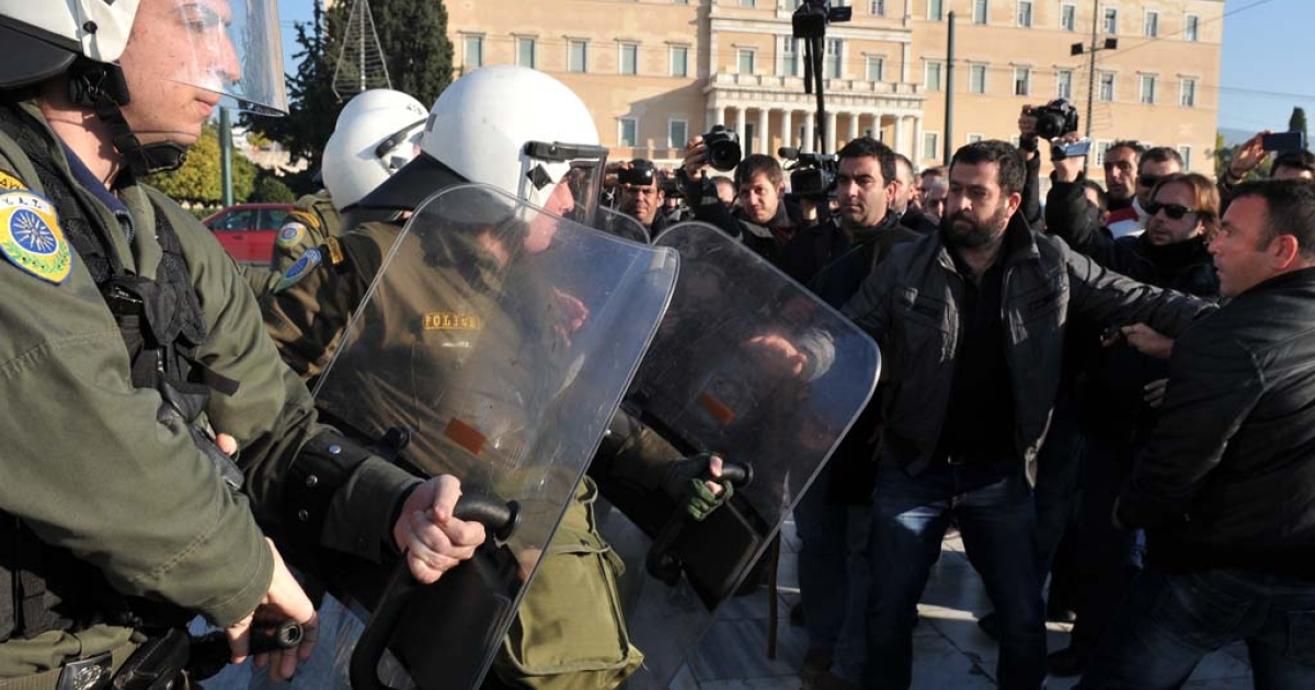 Angry farmers from southern Greek Crete island clash with police in front of the parliament on December 20, 2013.</p>
