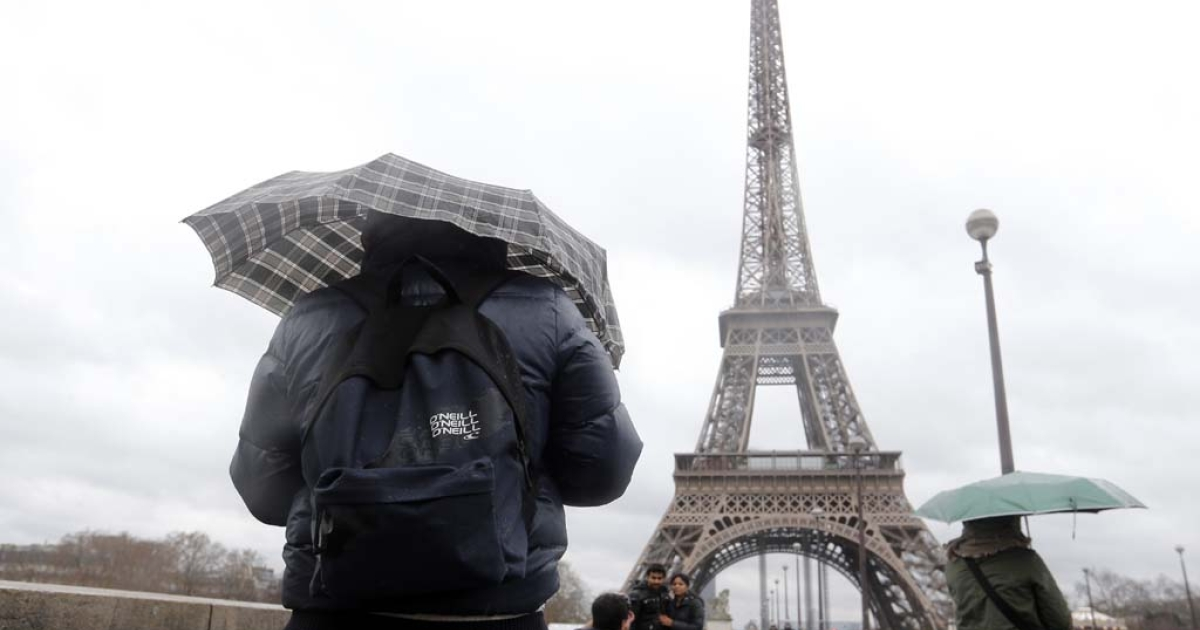 People walk toward the Eiffel Tower as rain falls and wind blows on December 24, 2013 in Paris. High winds and heavy rain battered parts of Europe since the eve.</p>