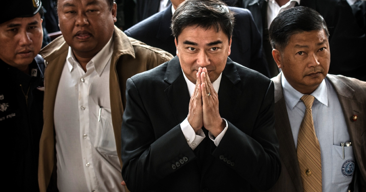 Former Thai prime minister Abhisit Vejjajiva (C) gestures as he arrives at the court in Bangkok on December 12, 2013.</p>