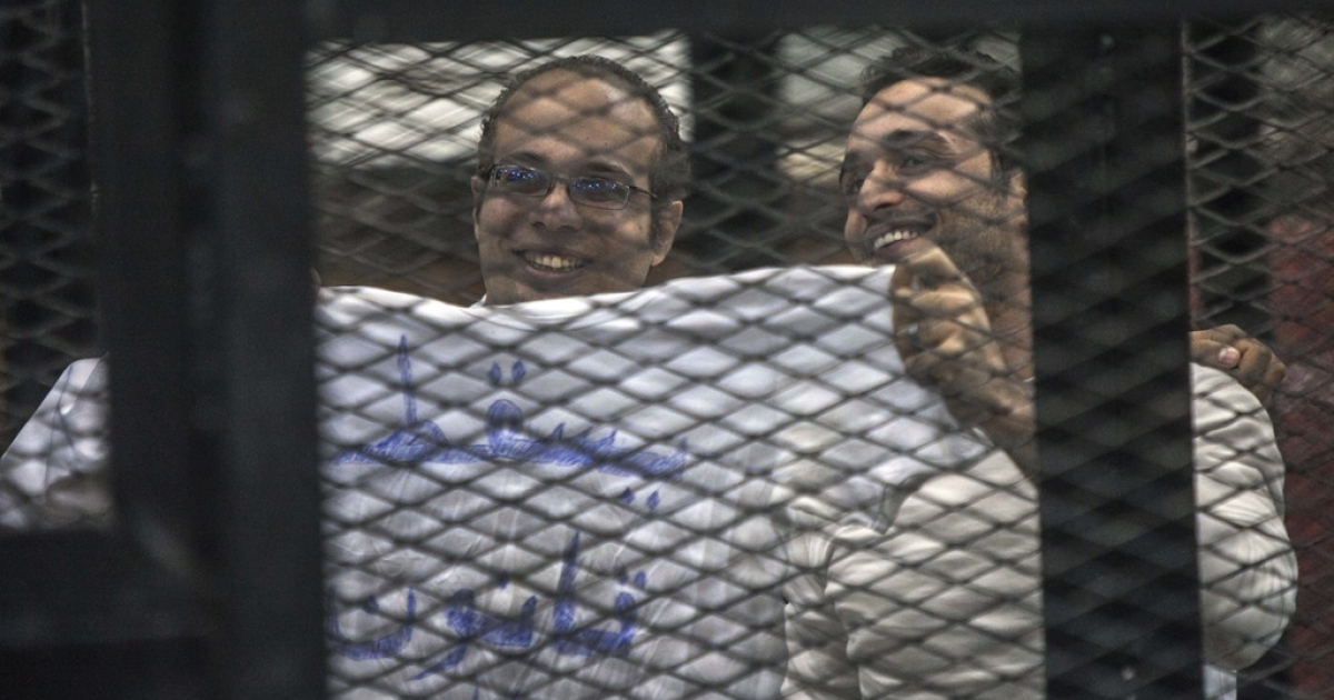 Political activist and coordinator of the April 6 Movement, Ahmed Maher and activist Ahmed Doma (R) show a T-shirt reading 'Dropping the law on demonstrations' during his trial on Dec. 8, 2013 in Cairo, Egypt.</p>