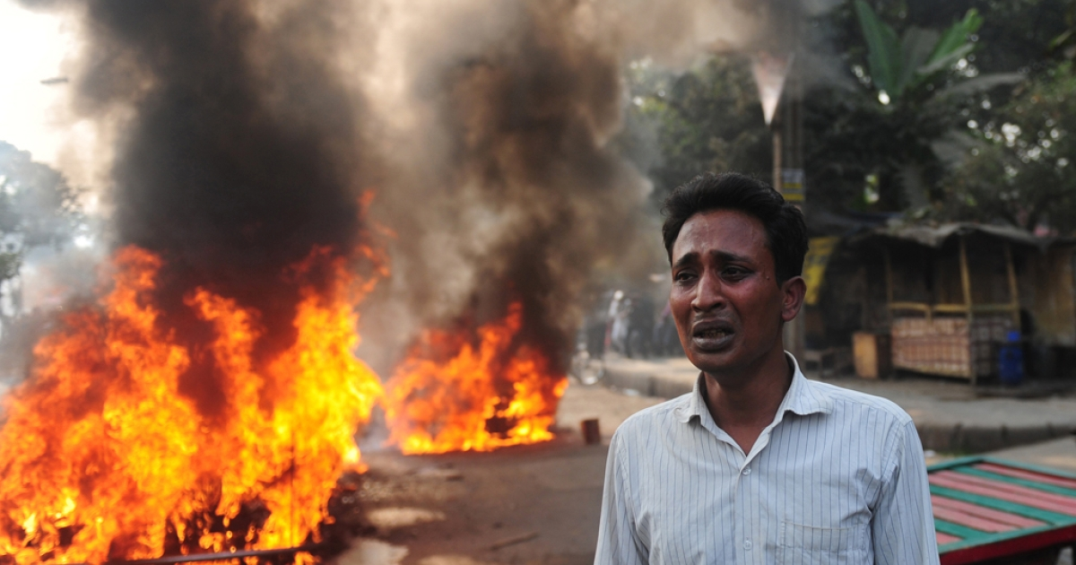 A Bangladeshi vehicle owner reacts near a burning car set on fire by demonstrating Jamaat-e-Islami supporters following the execution of Abdul Quader Molla, a top Islamist leader convicted of war crimes, in Dhaka on December 13, 2013.</p>