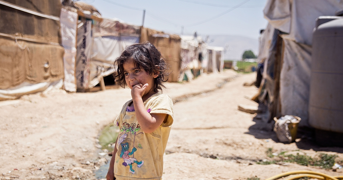 A Syrian girl stands between two rows of shacks in an informal refugee camp in the central Bekaa Valley of Lebanon.</p>
