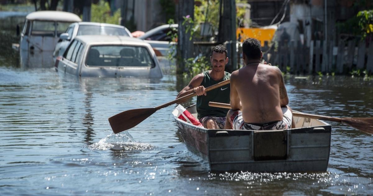 Men row in a boat along a flooded street in Vila Velha, Espirito Santo state, Brazil, on December 27, 2013.</p>