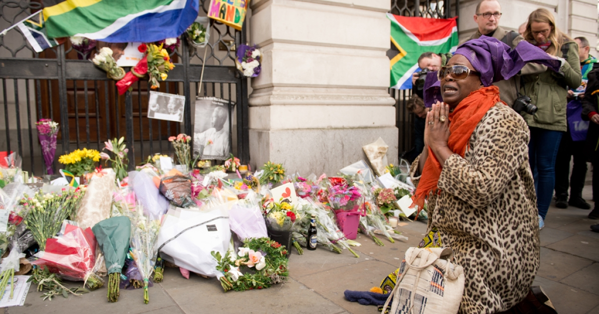 A woman kneels near to the floral tributes for late anti-apartheid fighter, Nobel Prize winner and South African President Nelson Mandela at the South African High Commisson in Trafalgar Square, central London on December 6, 2013.</p>