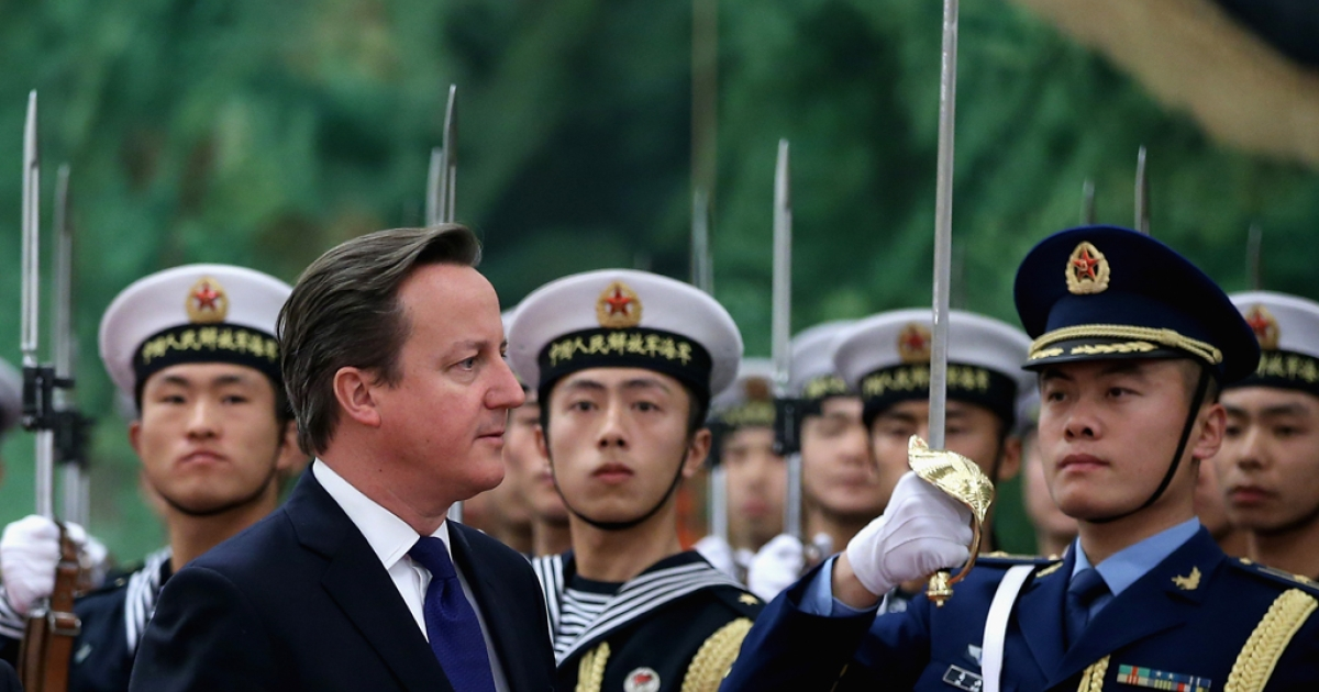 Chinese Premier Li Keqiang invites British Prime Minister David Cameron to view an honor guard during a welcoming ceremony inside the Great Hall of the People on December 2, 2013 in Beijing, China.</p>