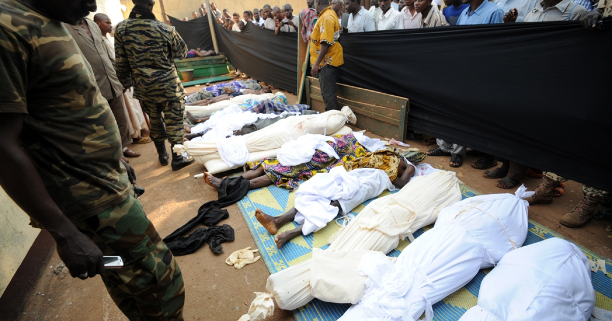 People stand near bodies found lying in a mosque and in its surrounding streets in the Central African capital Bangui on December 5, 2013, after overnight violence.</p>