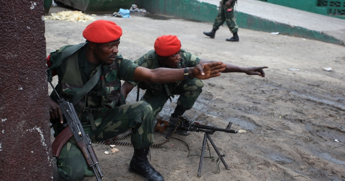 Military police gesture near the state broadcaster RTNC as gunfire erupted on Dec. 30, 2013 at the premises of the broadcaster in Kinshasa.</p>