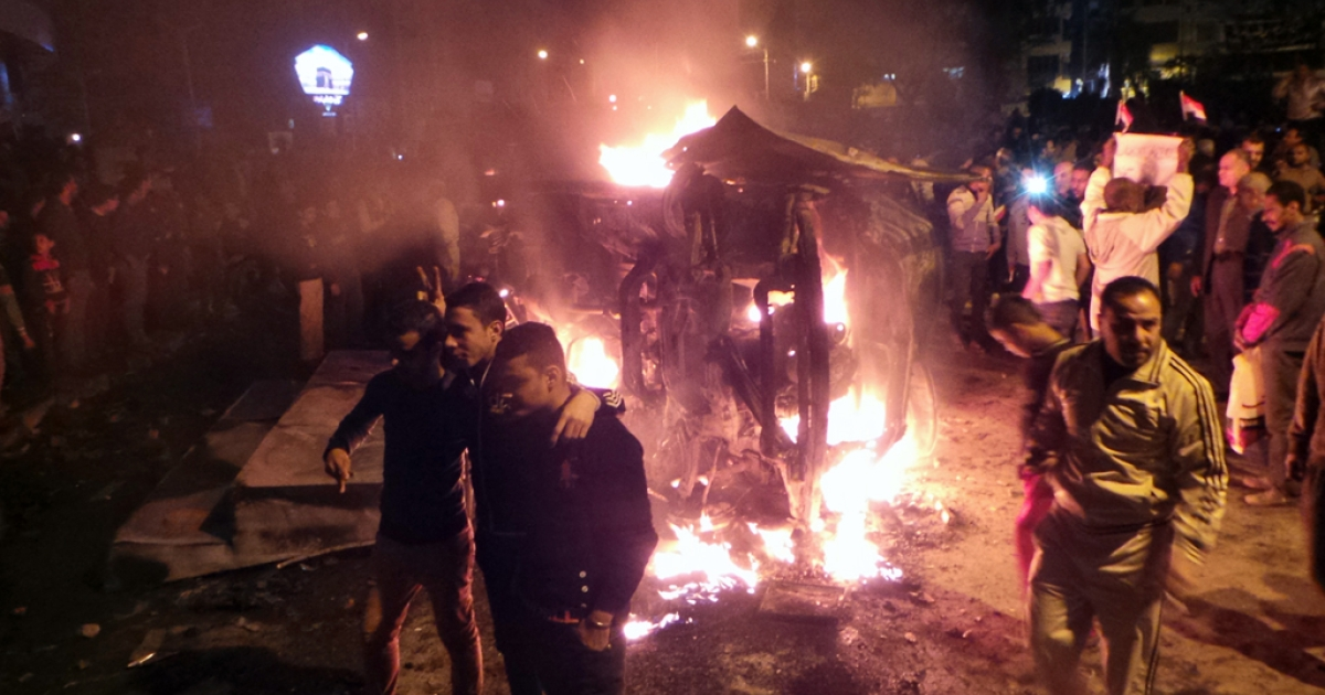 Angry Egyptians set fire to a microbus, said to be belong to a company owned by a businessman who supports the Muslim Brotherhood on December 24, 2013.</p>