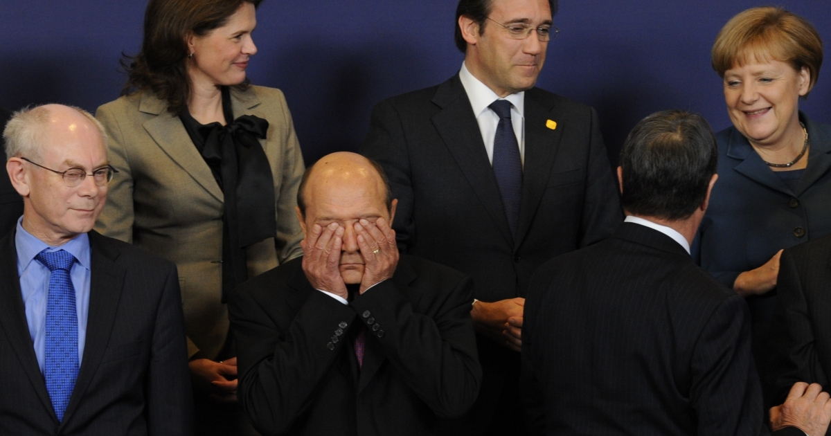 Waking up? Romanian President Traian Basescu (C) wipes his face at an EU summit last week.</p>