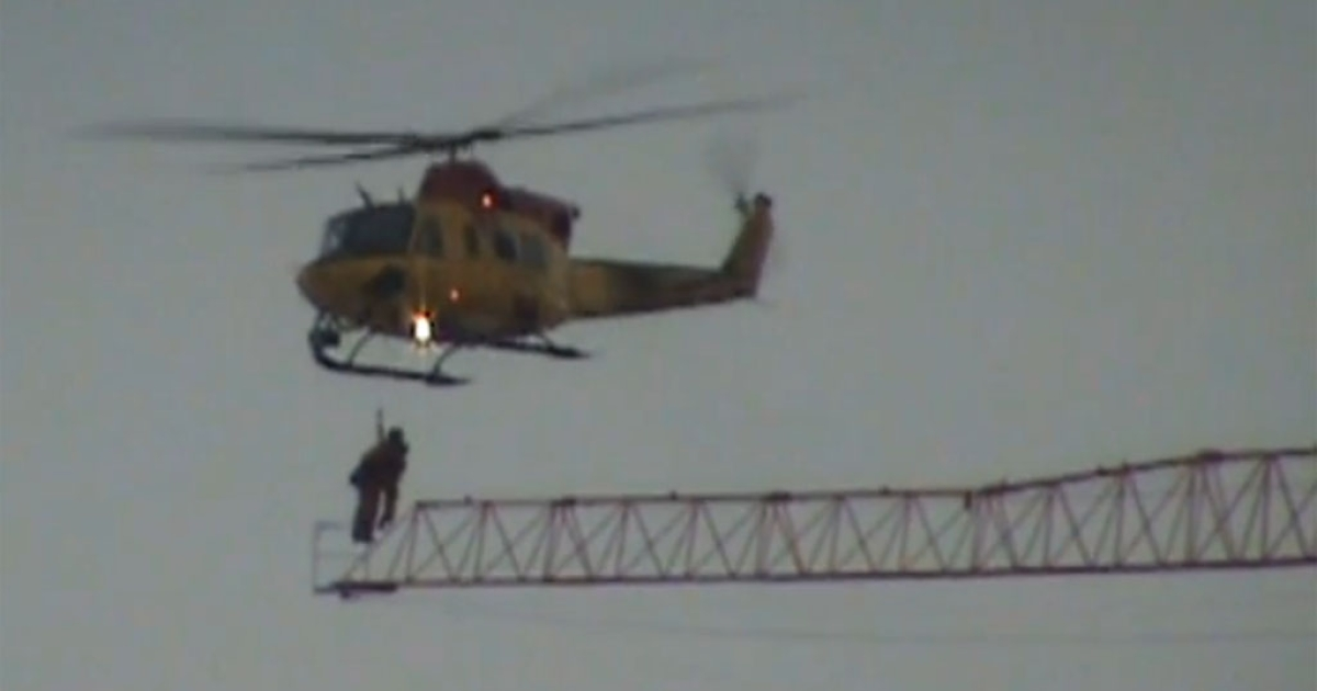 A military helicopter rescues a stranded crane operator as fire rages below in Kingston, Ont., on Dec. 17, 2013.</p>