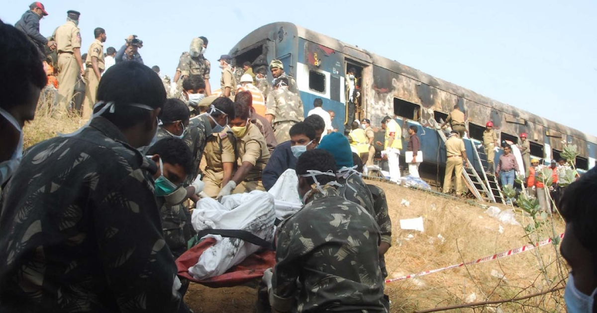 Indian rescue personnel use a stretcher to carry a body near a charred carriage of the Nanded-Bangalore Express near Puttapartihi in Ananthpur District some 300kms south of Hyderabad on December 28, 2013, after a fire engulfed the train.</p>