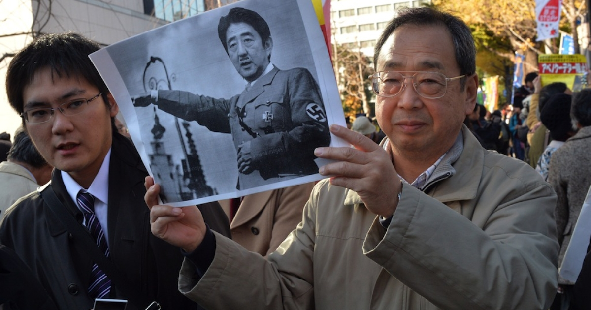 A civic group member holds a picture of Japanese Prime Minister Shinzo Abe morphed with the image of former German chancellor Adolf Hitler during a rally to protest against a controversial new state secrets bill in front of the National Diet in Tokyo on December 6, 2013.  A controversial state secrets bill became law in Japan Friday night despite objections from a broadening coalition who say the legislation is being rushed through parliament.</p>