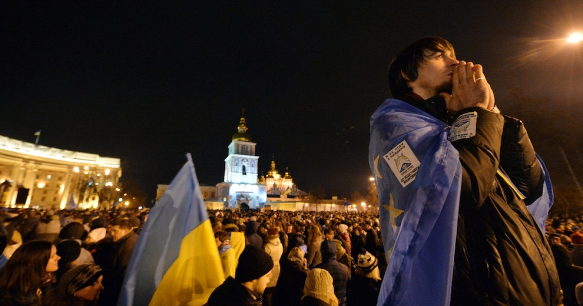 A protester, wearing a European Union flag, prays during a rally on Mykhayllivska Square in Kiev after police dispersed protesters on Independence Square on Nov. 30, 2013.</p>
