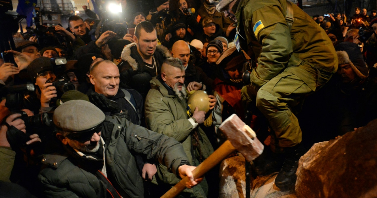 A protester breaks apart a statue of Lenin at a monument in his honor after it was pulled down during a mass rally called