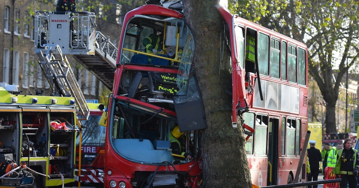 Emergency workers use a cherry picker to reach passengers trapped inside the wreckage of a bus that crashed into a tree in London on Dec. 20, 2013.</p>