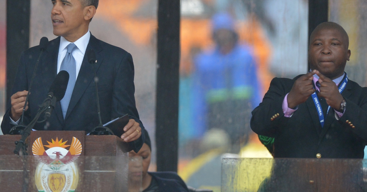 President Barack Obama delivers a speech next to a sign language interpreter (R) during the memorial service for late South African President Nelson Mandela at Soccer City Stadium in Johannesburg. South Africa's deaf community has accused the interpreter of being a fake who had merely flapped his arms around during speeches.</p>