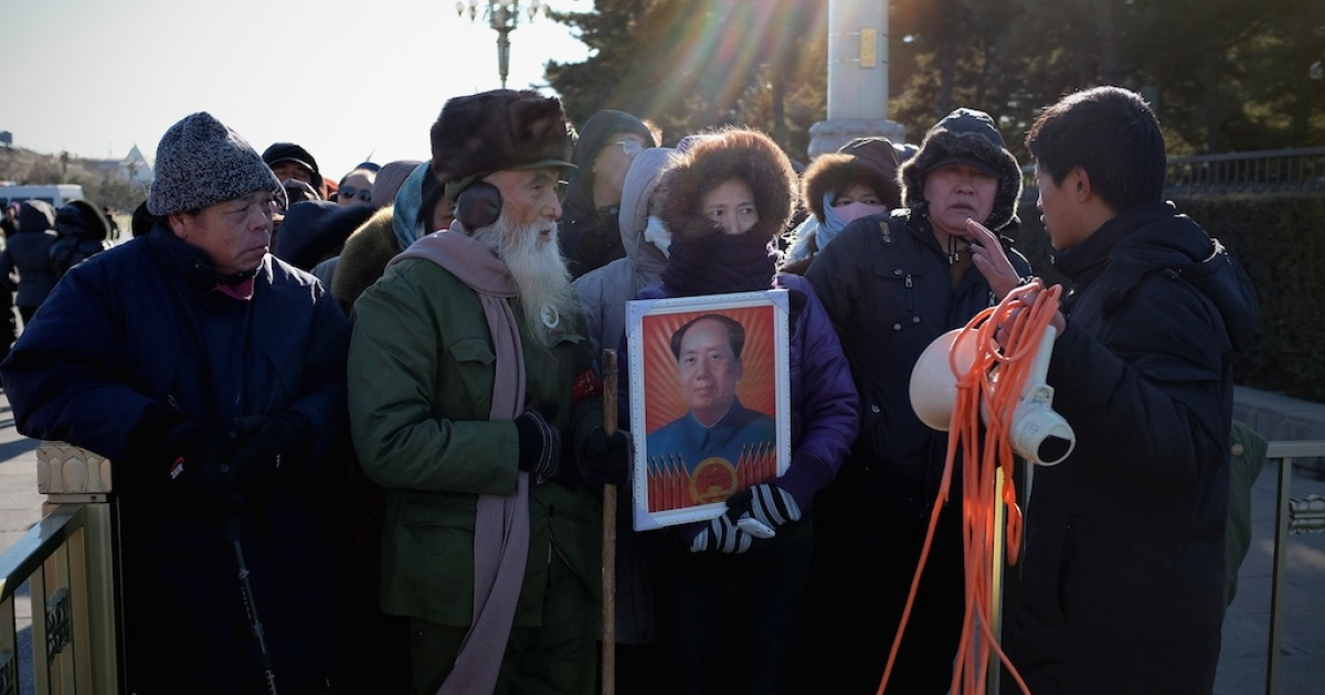 Chinese people stand in line to enter Mao Zedong's mausoleum in Tiananmen Square on Dec. 26, 2013 in Beijing, China.</p>