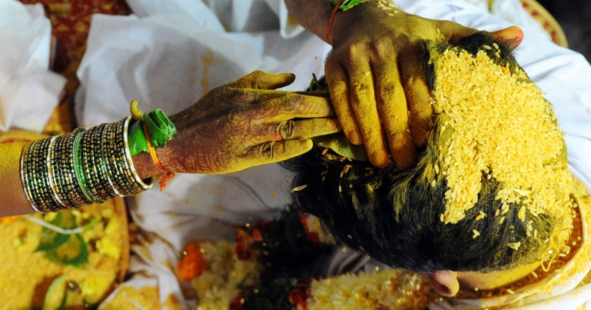 An Indian bride and groom smear yellow rice - Talambralu - on their heads during a mass wedding ceremony in 2009.  Many Indians consider their wedding day the most important of their life. A matchmaking service helps HIV+ people who want to get married.</p>