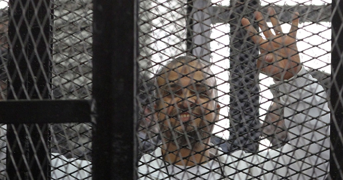 Muslim Brotherhood member Mohamed Beltagy holds up four fingers, called rabaa (four) in Arabic, from the defendants' dock in a Cairo courtroom December 11, 2013. The trial of Egypt's Muslim Brotherhood chief Mohamed Badie and his deputies came to an abrupt end when judges walked out, citing chaos in the dock.</p>