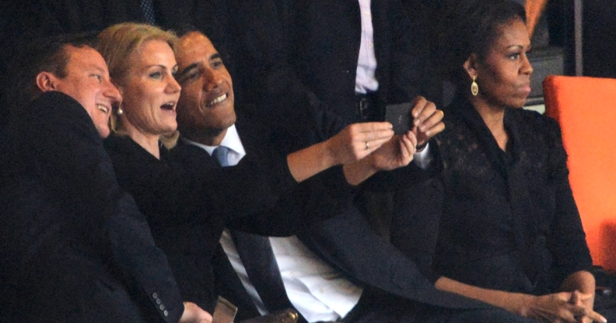 President  Barack Obama (R) and British Prime Minister David Cameron pose for a picture with Denmark's Prime Minister Helle Thorning Schmidt (C) during Nelson Mandela's memorial service on Dec. 10, 2013, in Johannesburg. First lady Michelle Obama (R) does not look pleased.</p>