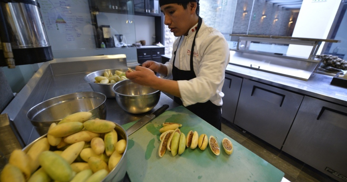 An assistant cook works on exotic fruits in the kitchen of the Central Restaurant in the trendy district of Miraflores in Lima, Peru on Sept. 7, 2013.</p>