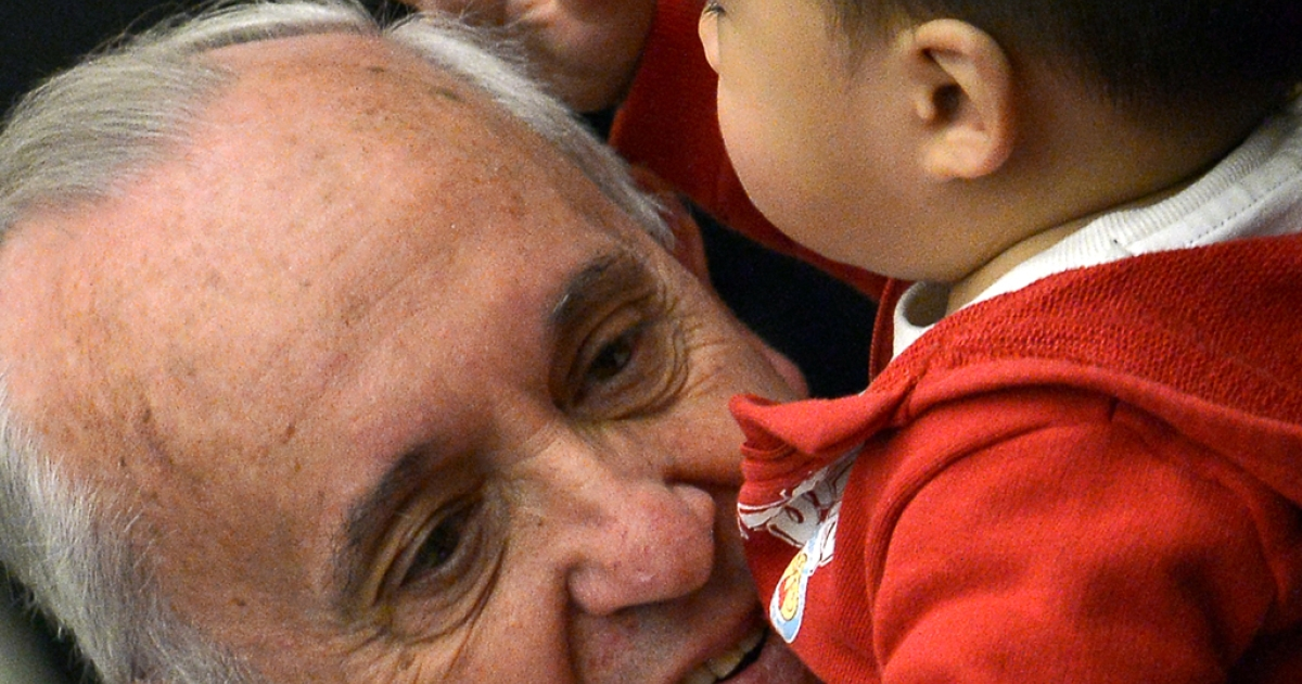 A child caresses Pope Francis' head during an audience with beneficiaries and volunteers of the Santa Marta Pediatric Dispensary in the Vatican on Dec. 14, 2013.</p>