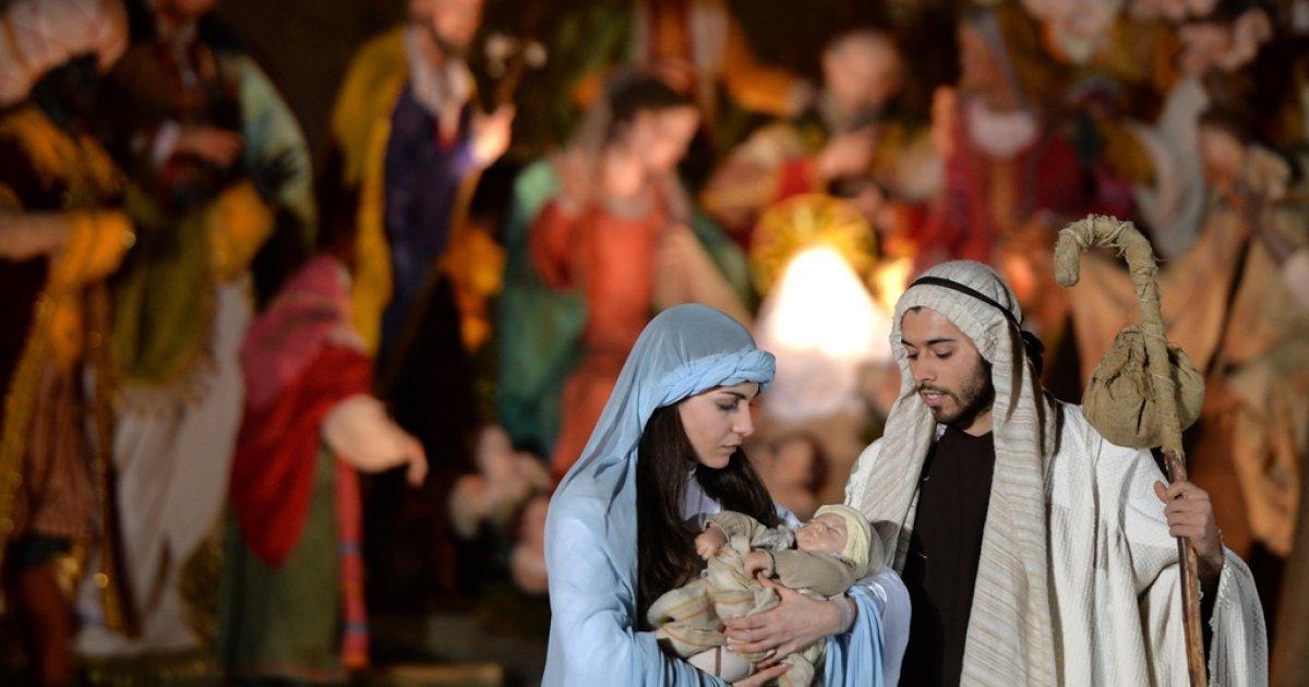 People play a nativity scene during the unveiling ceremony of the crib in St. Peter's Square at the Vatican, on December 24, 2013.</p>