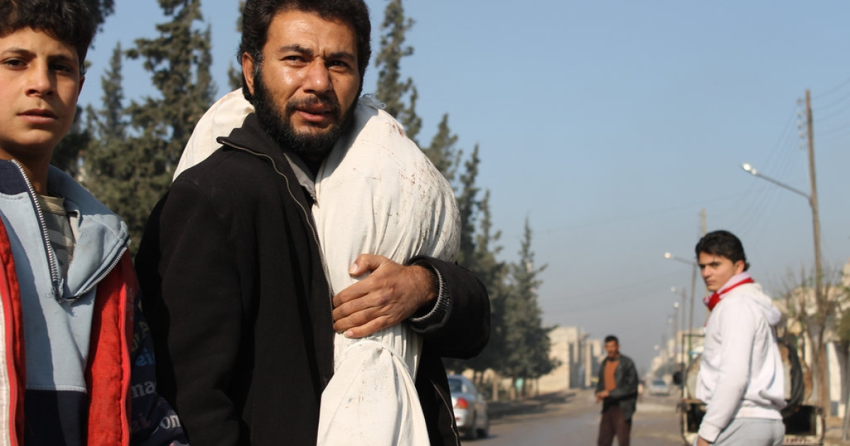 A Syrian man carries body wrapped in shrouds over his shoulder following airstrikes on a rebel area of the war-torn northern city of Aleppo on December 15, 2013. The Aleppo Media Centre, an activist network on the ground, reported several helicopter attacks on rebel areas of the city, once Syria's economic hub.</p>