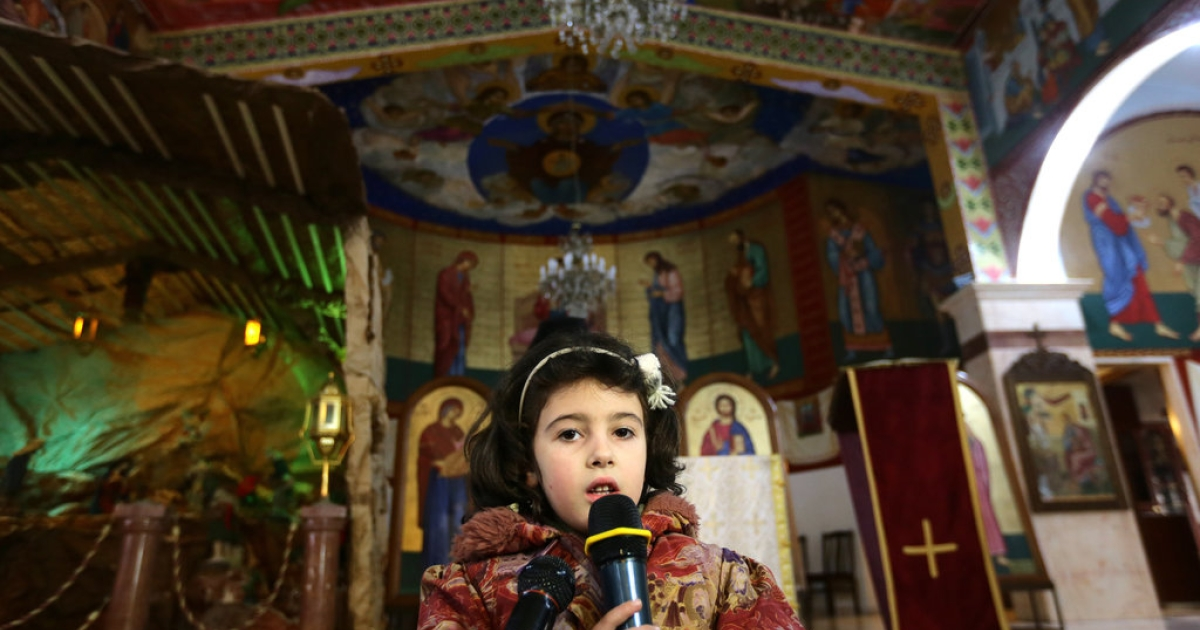 A Syrian girl from the Christian town of Maalula, a symbol of the ancient Christian presence in Syria which is currently under control of Syrian rebels, including jihadist groups, speaks during a service at the St. Joseph church in Damascus, on December 18, 2013. Syrian Melkite Greek Catholic Patriarch Gregory III Laham, has called on his fellow Christians to stay in Syria, despite the brutal conflict raging in the country. According to the patriarch, 450,000 Syrian Christians have been displaced by the conflict that began in March 2011, around 40,000 of whom have fled to Lebanon.</p>