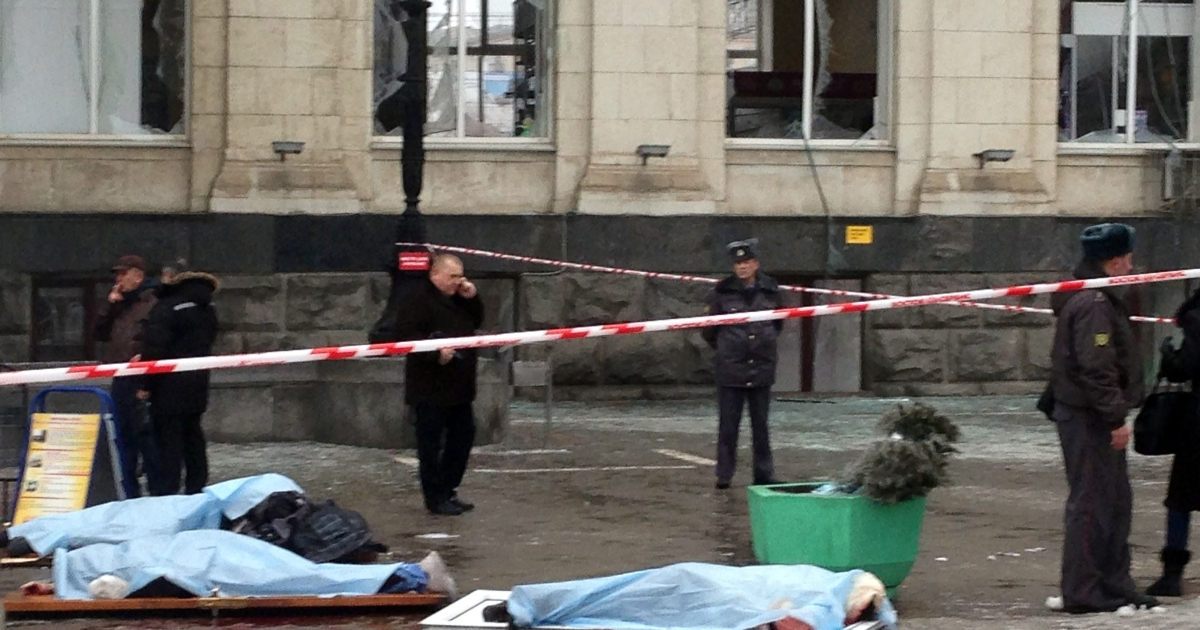 The covered bodies of victims lie on the ground as Russian security personnel inspect the damage at a train station following a suicide attack in the Volga River city of Volgograd on Dec. 29, 2013.</p>