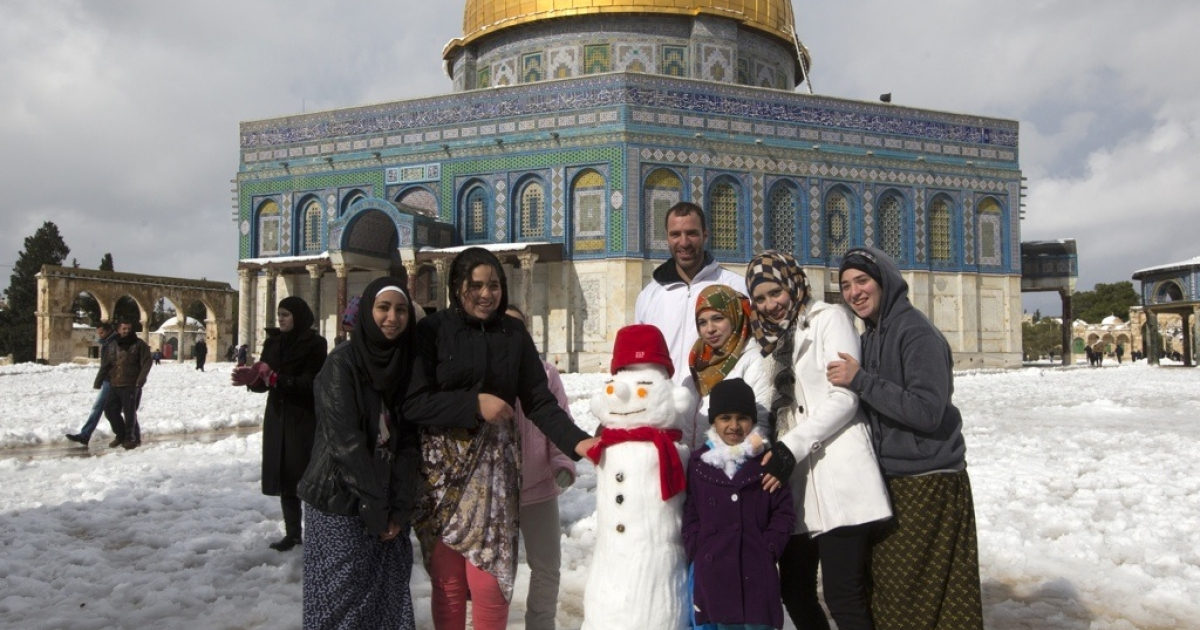 Palestinians pose for a photograph next to a snowman in front of the Dome of the Rock at the Al-Aqsa mosque compound in the Old City of Jerusalem on Dec. 13, 2013.</p>