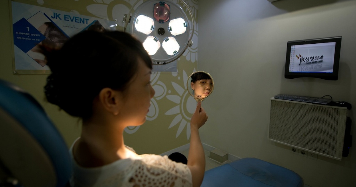 A Vietnamese-American patient checks her appearance four days after undergoing a cosmetic rhinoplasty and eye procedures at the JK Medical Group plastic surgery hospital in Seoul.</p>