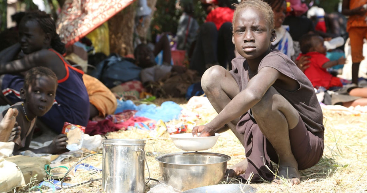 A young girl displaced following recent fighting in Juba, South Sudan, prepares a meal inside the UNMISS compound on December 17, 2013 on the outskirts of the capital.</p>