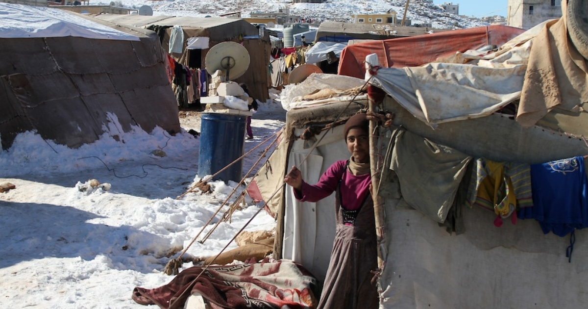 A Syrian child stands behind a tent in a refugee camp on Dec. 15, 2013, in the town of Arsal in the Lebanese Bekaa valley.</p>